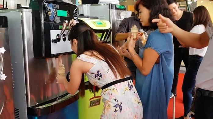 Người tiêu dùng thích thú thưởng thức kem tươi trong siêu thị.